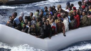 Migrants sit in a boat during a rescue operation by the Italian navy off the coast of Sicily on Nov. 28. Italy is looking to revamp the way it handles the hundreds of thousands of migrants who arrive annually.